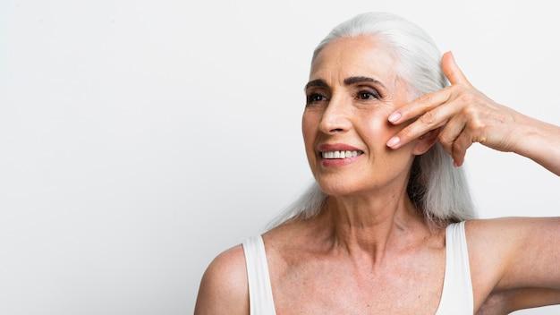 Hermosa mujer senior aplicando tratamiento