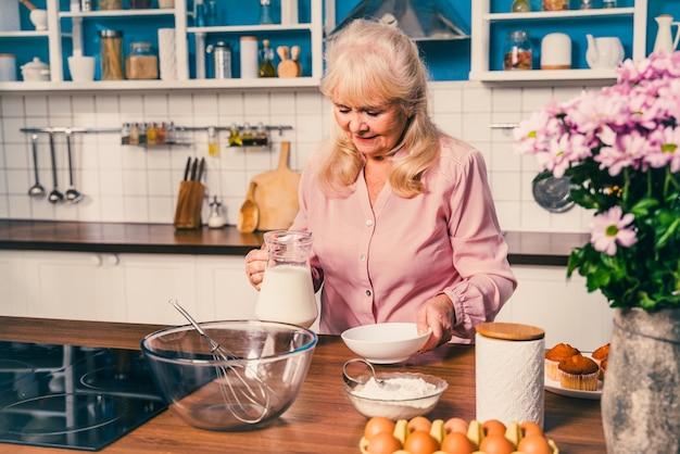 Hermosa mujer senior para hornear en la cocina