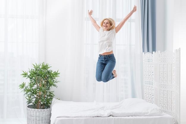 Hermosa mujer senior saltando en la cama