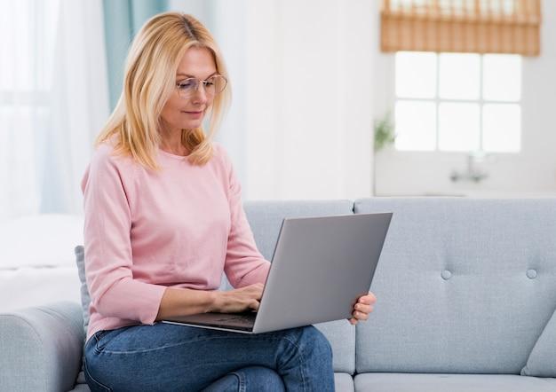 Hermosa mujer senior sosteniendo una laptop