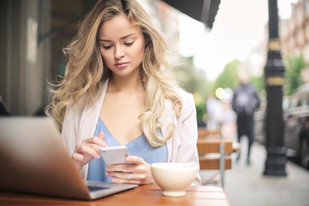 Hermosa mujer sentada en un bar, trabajando con su computadora portátil