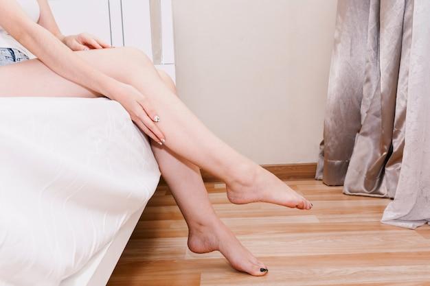 Hermosa mujer sentada en la cama y tocar su piel en las piernas