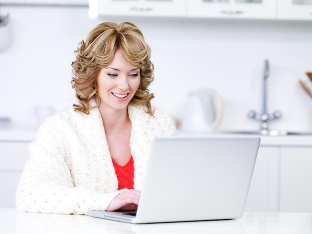 Hermosa mujer sentada en la cocina y usando la computadora portátil - en el interior