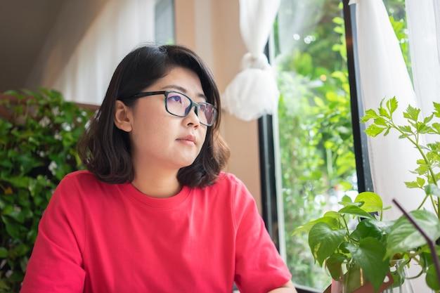 Una hermosa mujer sentada, mirando a otro lado, mirando por la ventana, sintiéndose sola y sola.