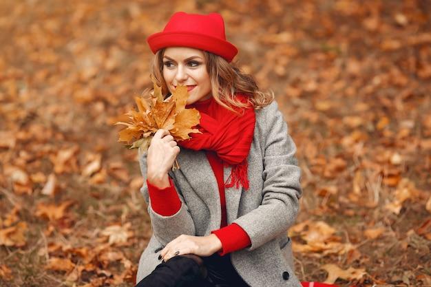 Hermosa mujer sentada en un parque de otoño