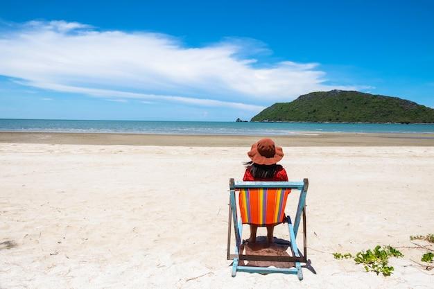 Hermosa mujer sentada en una silla en el mar en el verano