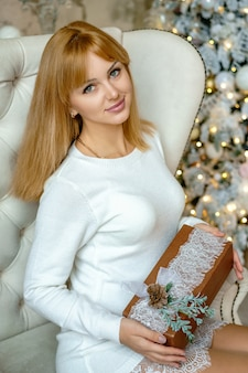 Hermosa mujer sentada en una silla con un regalo cerca del ambiente festivo del árbol de navidad