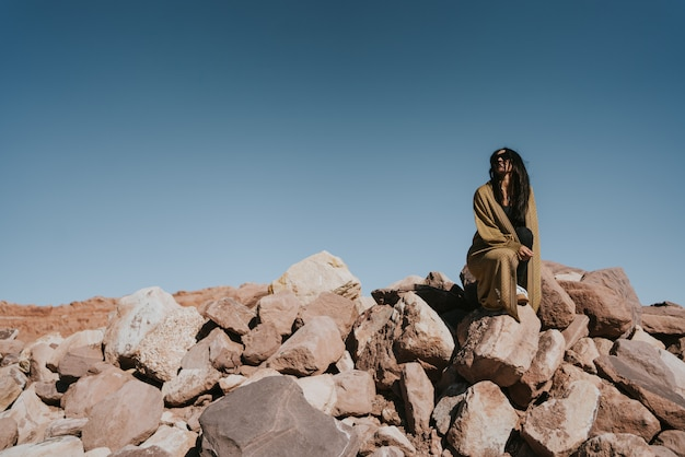 Hermosa mujer sentada sobre un montón de rocas