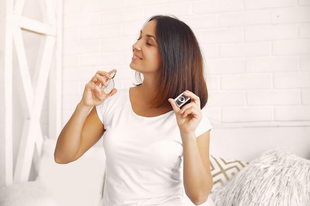 Hermosa mujer sentada en su casa en una cama y usando perfume