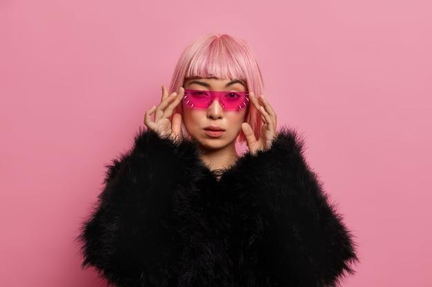 Hermosa mujer seria segura de sí misma usa gafas de sol rosas de moda, tiene el cabello rosado, vestida con un suéter negro cálido y esponjoso, se para en el interior, piensa en algo. mujeres, moda, concepto de estilo.