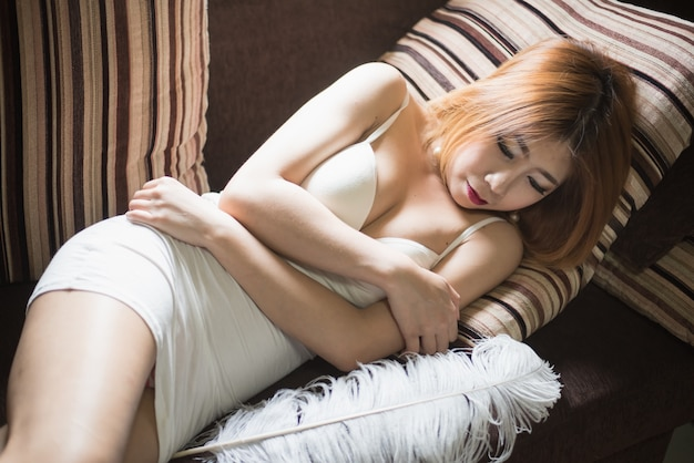 Hermosa mujer sexy asiática debajo de las mujeres modela en la cama