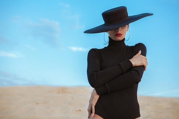 Hermosa mujer sexy bailando en la arena en el desierto