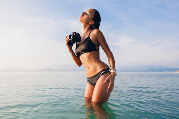 Hermosa mujer sexy, cuerpo delgado perfecto, piel bronceada, traje de baño bikini negro, de pie en el agua azul, sosteniendo una cámara de fotos digital, vacaciones de verano calientes y tropicales, tendencia de moda, cintura, vientre, caderas