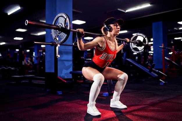 Hermosa mujer sexy deportiva con gorra y auriculares haciendo ejercicio en cuclillas en el gimnasio