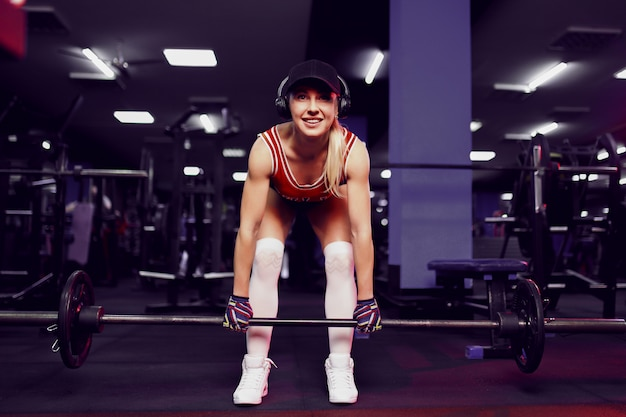Hermosa mujer sexy deportiva en gorra haciendo ejercicio en cuclillas en el gimnasio