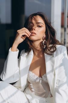 Hermosa mujer sexy joven, chica glamorosa en la elegante chaqueta blanca, corsé, traje
