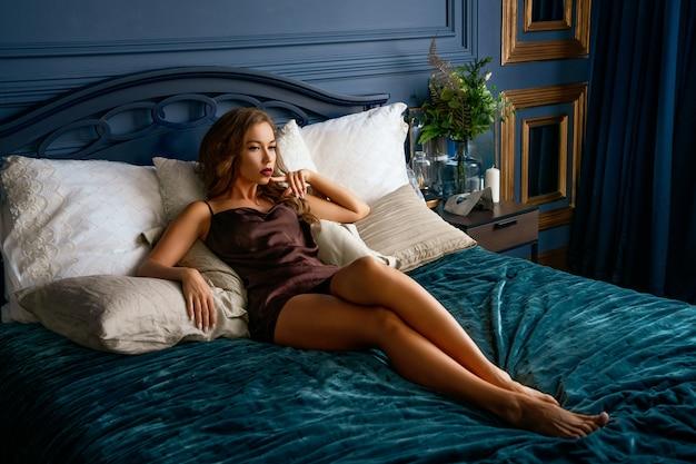 Una hermosa mujer sexy con un maquillaje brillante está acostada en ropa interior en la cama