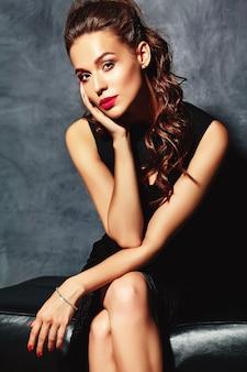 Hermosa mujer sexy modelo dama con labios rojos en elegante vestido negro sentado en el sofá cerca de la pared gris
