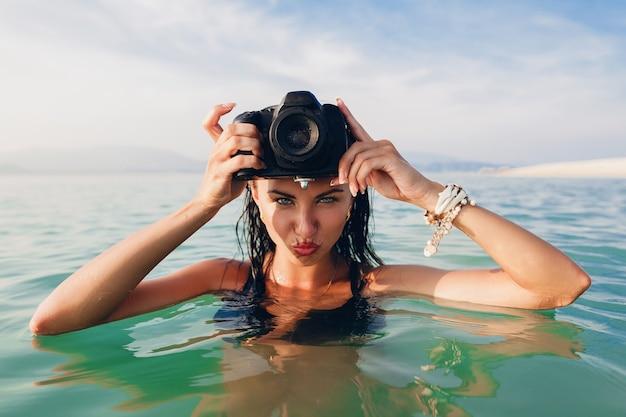 Hermosa mujer sexy, piel bronceada, traje de baño bikini negro, de pie en el agua azul, sosteniendo una cámara de fotos digital, vacaciones de verano caliente, tropical, tendencia de moda, coqueta, mojada