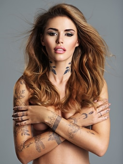 Hermosa mujer sexy con un tatuaje en el cuerpo. retrato de joven adulta sexy con cabello castaño. mujer sexy con cuerpo desnudo y brazos cruzados sobre un pecho.
