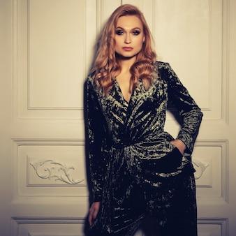Hermosa mujer sexy usa ropa de traje de terciopelo para el estilo de oficina de empresaria está de pie cerca de la puerta