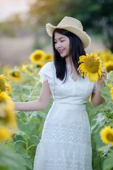 Hermosa mujer sexy con un vestido blanco caminando en un campo de girasoles