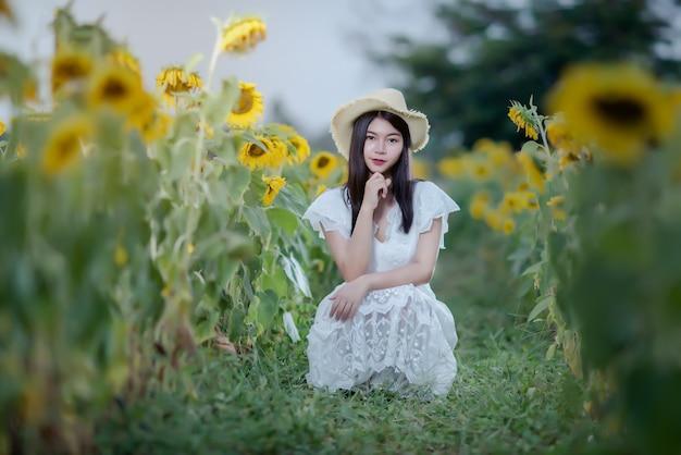 Hermosa mujer sexy con un vestido blanco en un campo de girasoles, estilo de vida saludable