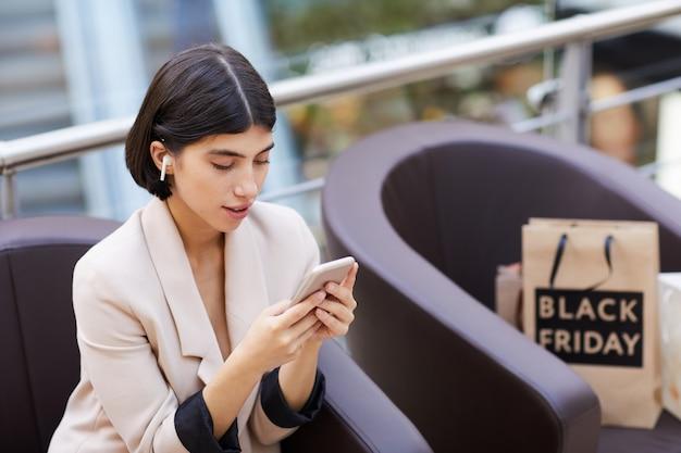 Hermosa mujer con smartphone mientras se relaja en el centro comercial