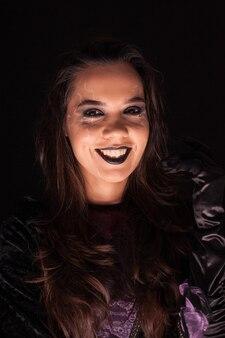 Hermosa mujer sobre fondo negro vestida como una bruja aterradora para halloween.