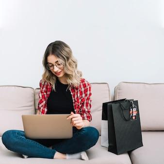 Hermosa mujer en el sofá de compras en línea