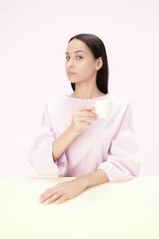 Hermosa mujer solitaria sentada en el estudio rosa y mirando triste sosteniendo la taza de café en la mano.