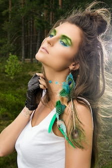 Hermosa mujer con sombras de ojos verdes y aretes de plumas