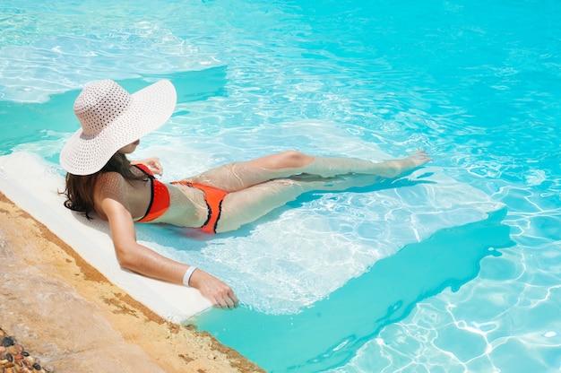 Hermosa mujer sombrero blanco y bikini acostada en una piscina