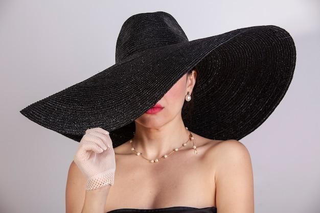 Hermosa mujer con sombrero, guantes, joyas y labios rojos. moda retro