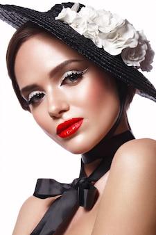 Hermosa mujer con un sombrero negro con flores y maquillaje retro
