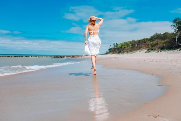 Hermosa mujer con sombrero de paja y traje de baño blanco y falda caminando por la línea de surf en la playa cerca de las olas.