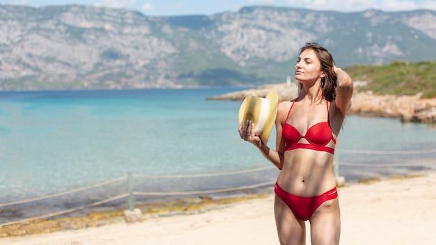 Hermosa mujer con un sombrero de pie en la playa