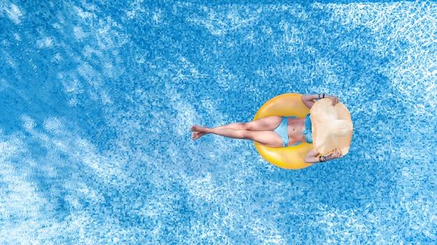 Hermosa mujer con sombrero en la piscina vista aérea superior desde arriba