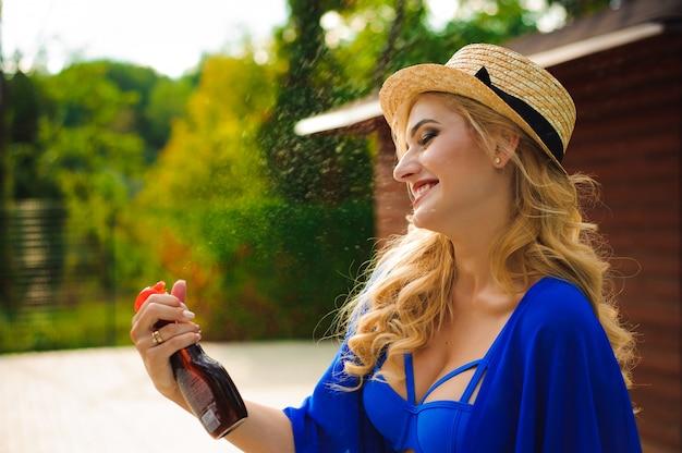 Hermosa mujer con sombrero sentado cerca de una piscina y aplicar spray de protección solar en su cuerpo.