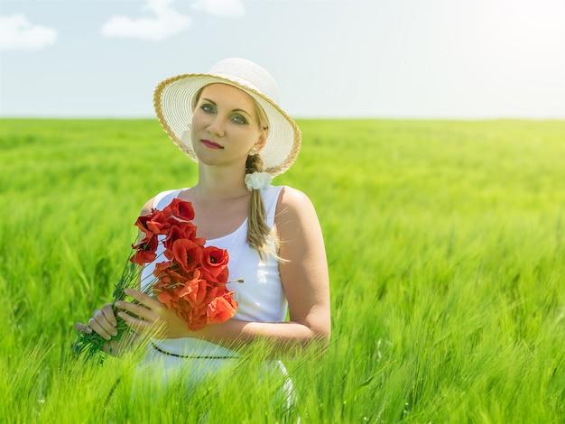 Hermosa mujer con sombrero en el sol en un campo de centeno.