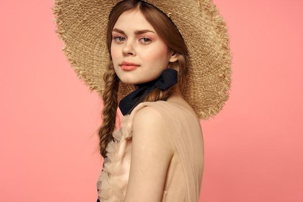 Hermosa mujer con sombrero y vestido negro modelo de fondo rosa retrato de cinta