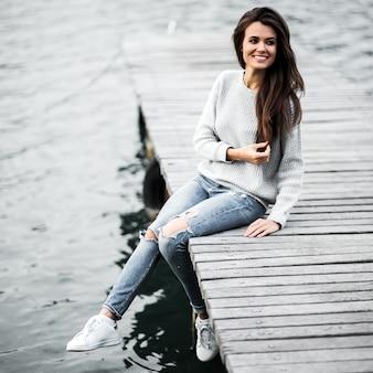 Hermosa mujer soñando sentado en el muelle junto al lago.