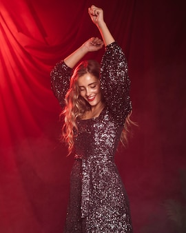 Hermosa mujer sonriendo y bailando sobre un fondo de cortina roja