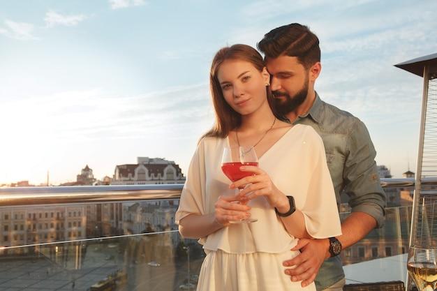 Hermosa mujer sonriendo a la cámara mientras su novio la abraza en el balcón al atardecer