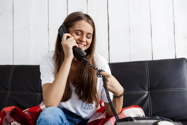 Hermosa mujer sonriendo, hablando por teléfono, sentado en el sofá.