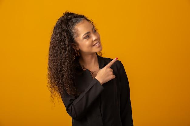 Hermosa mujer sonriendo con un peinado afro y señalando
