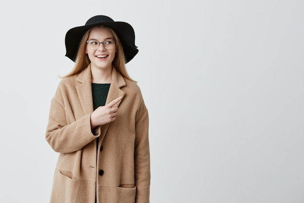 Hermosa mujer sonriente en abrigo sobre suéter verde y anteojos apuntando a la pared blanca en blanco mientras demuestra algo. hembra joven alegre que indica con el dedo delantero en fondo gris.