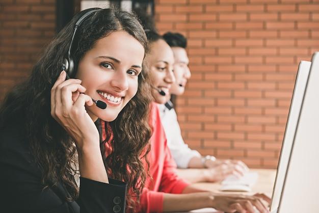 Hermosa mujer sonriente agente de servicio al cliente de telemarketing trabajando en call center con su equipo