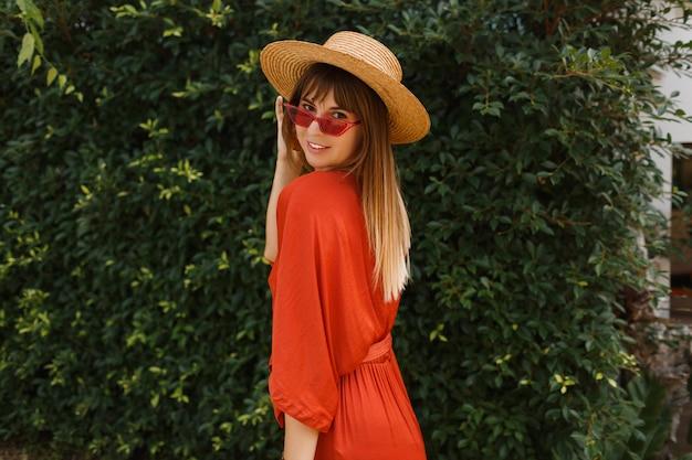Hermosa mujer sonriente en elegantes gafas de sol rojas y vestido naranja posando al aire libre sobre jardín tropical.