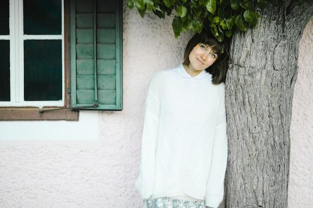 Hermosa mujer sonriente se encuentra junto al árbol